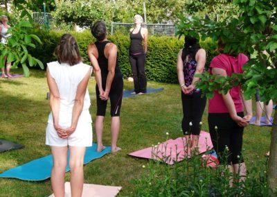 stehende Rückbeuge Variation, bei einer Garten Yoga Stunde